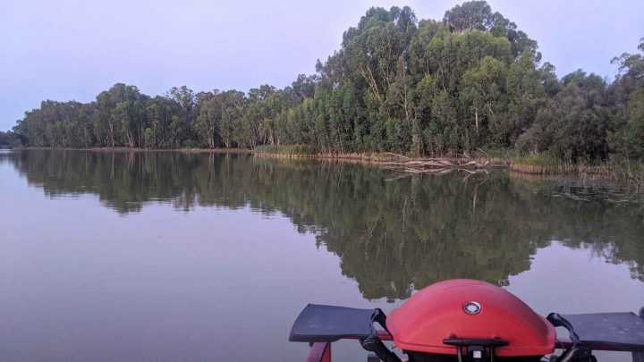 A view from the back deck of a houseboat to the river with a barbecue in the foreground